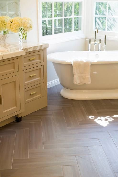 Stunning bathroom boasts a gray washstand adorned with brass pulls topped with thick white marble ...