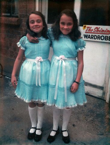 Lisa and Louise Burns, who played the Grady Twins in The Shining, pose in their costumes outside the film's Wardrobe Department.