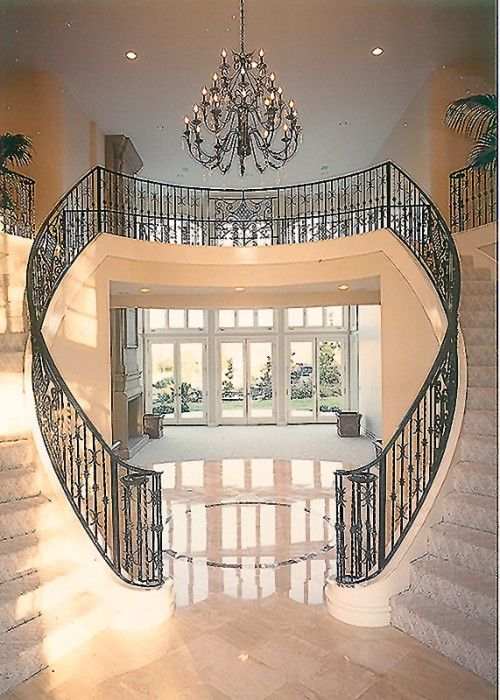 A beautiful double staircase with a wrought iron railing graces the entry of this Mediterranean style home  (via For the Home / Wowzers)