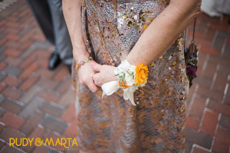 mother of the bride wears an elegant wrist corsage of white scabiosa and orange ranunculus on a cuff of cream satin ribbon.
