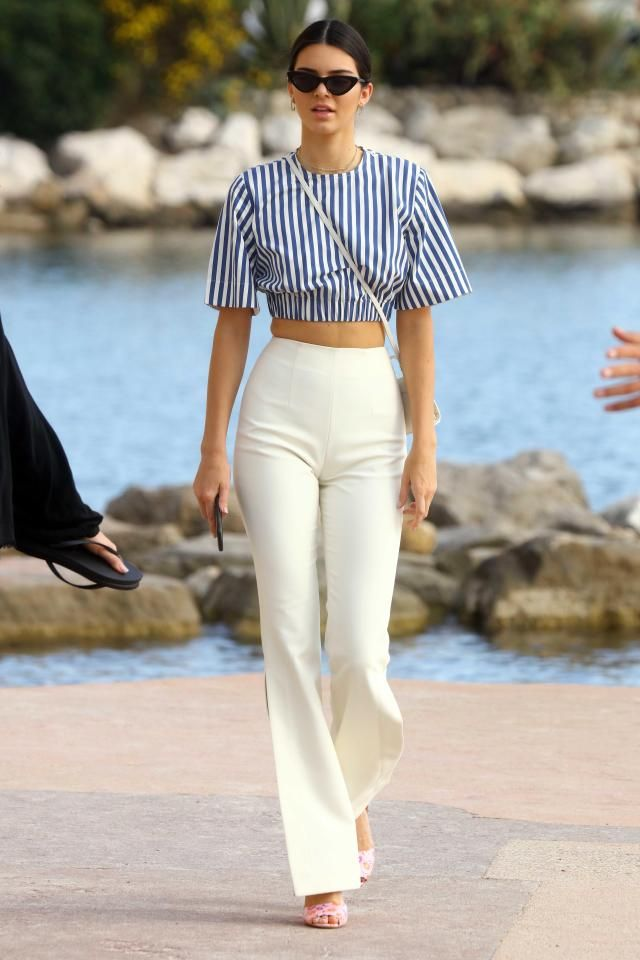 Kendall Jenner's legs look endless in a pair of fitted white trousers as she hits the beach in Cannes