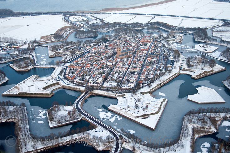 Naarden is a town built within a star fort, complete with fortified walls and a moat. During winter, the defences that once protected the town freeze over.
