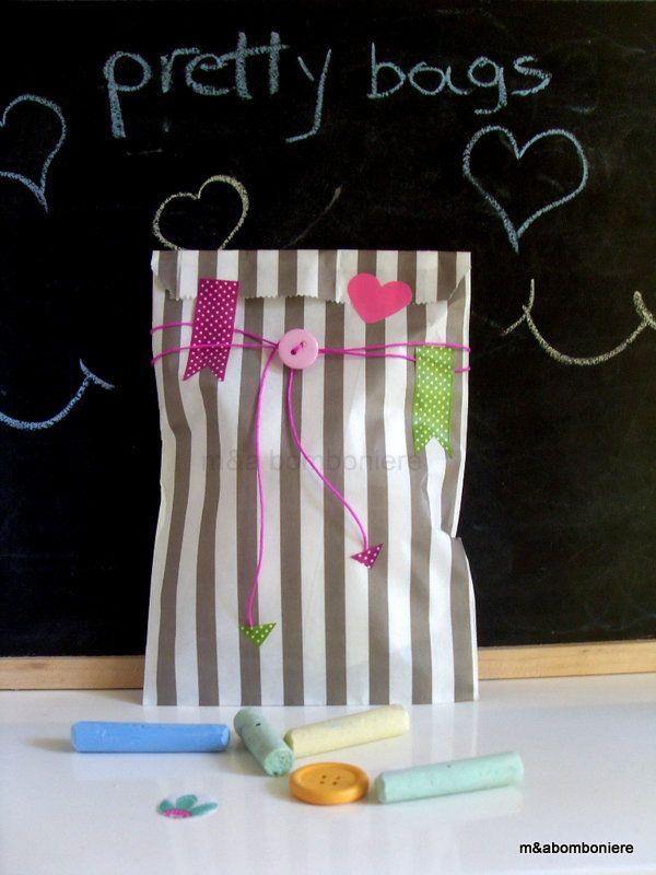 Γκρι ριγέ σακουλάκι με χάρτινες καρδούλες, πουά washi tape, κορδονάκι και ροζ κουμπάκι. Τιμή: 1,50 ευρώ.