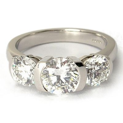 Three stone engagement ring in modern reveal half bezel setting in solid platinum featuring 2.5ctw of matching round diamonds