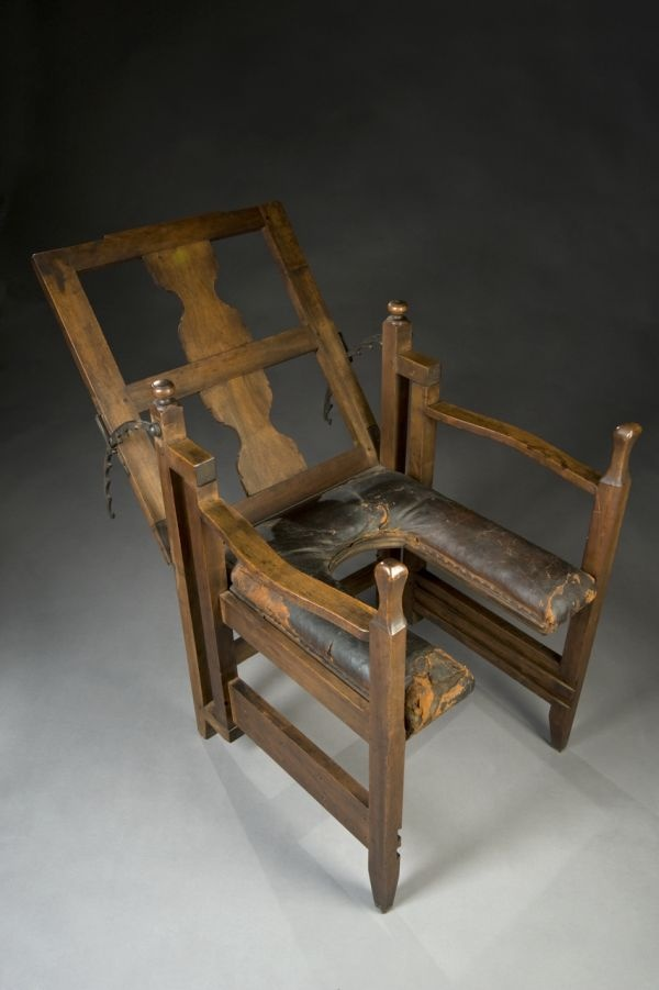 Adjustable Birthing Chair, c. 1750 onwards. Childbirth is made more comfortable for the mother by the adjustable seat, back and arms of the chair. Made from wood, padded leather and iron. The seat shape allows a clear route for the emerging baby and access for those assisting the birth. The chair is also known as a parturition chair. They were used from ancient times until the 1800s. The grooved parts on the bottom of the frame were used as leg rests, and for support and to press against.