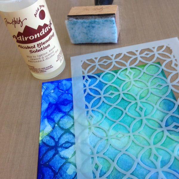 Use blending solution swirled on through stencil to remove alcohol ink and create pattern.