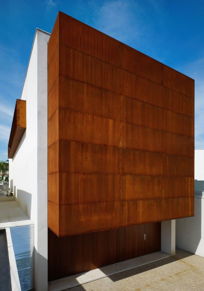 Gallery of Corten House / Marcio Kogan - 9.  I like these materials - stone gable, corten sides and roof with hidden gutters and the pool house a smooth rendered white.