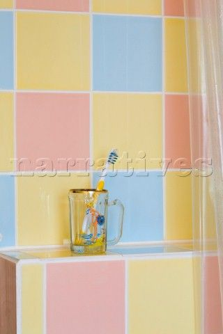 Toothbrush in glass cup with multicoloured pastel tiles in bathroom of Rye home  East Sussex  Englan