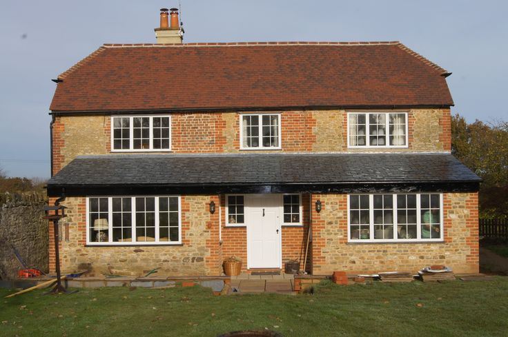 White aluminium windows with external Georgian bars where installed to retain the look of the original windows in this cottage