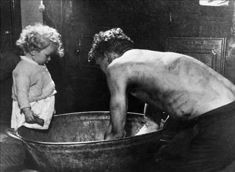 Miner washing at home in tin bath - before the days of the pithead baths.