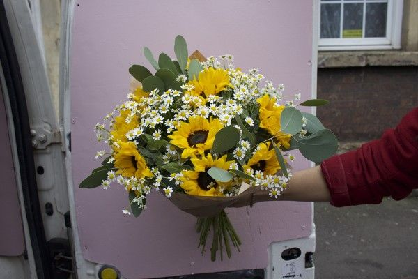 A big ol' bouquet containing Sunflowers, Tanacetum and Eucalyptus