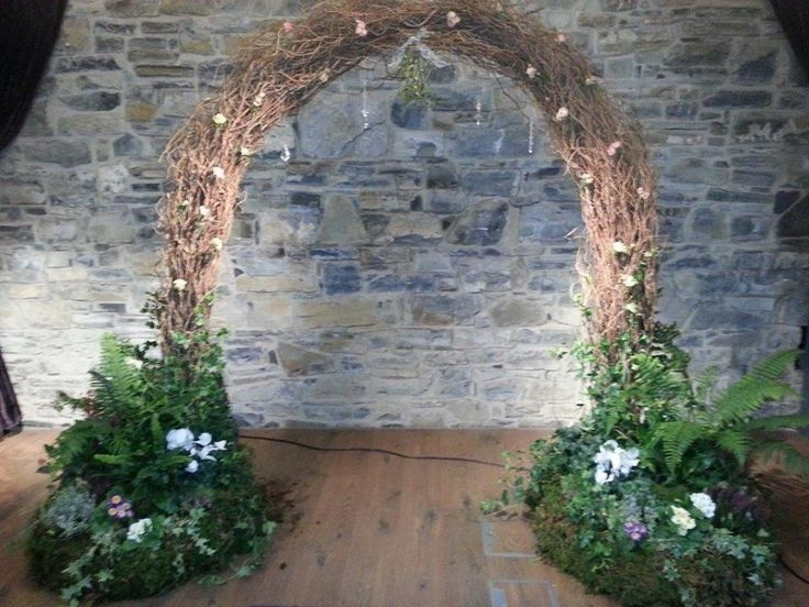 Rustic arch made with birch branches with a selection of ferns, seasonal flowers and hedera at the base.