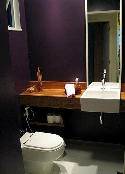 Lavabo com parede preta e bancada em madeira para contrastar
