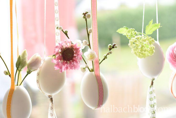Simple, aber bezaubernde Osterdeko-Idee: Hängende Mini-Vasen aus Gänseeiern mit pastellbunten Bändern und zarten Frühlingsblühern - für pure Vorfreude!