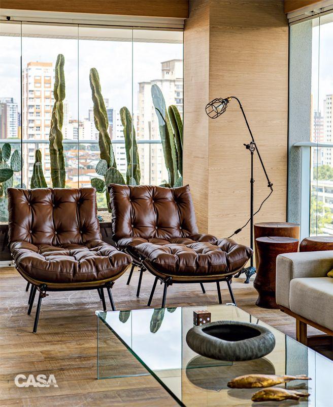Madeira aquece a área social integrada após a reforma - Clássicos do mobiliário, como as poltronas Costela (Desmobilia), criadas nos anos 1950 por Martin Eisler (1913-1977), colaboram na criação do ar cosmopolita.