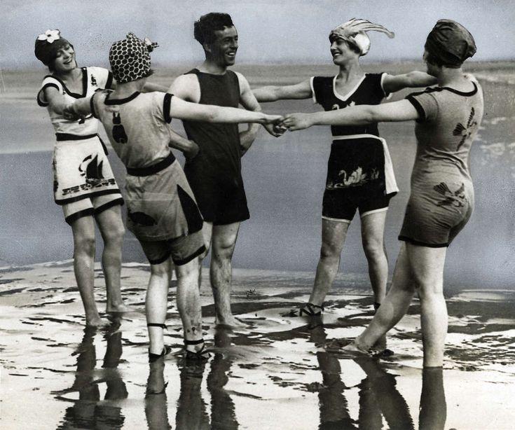 Badmode, badpakken, zwempakken. Vier jongedames en een heer gekleed in de nieuwe badmode namelijk beschilderde badpakken. Plaats onbekend, 1920.