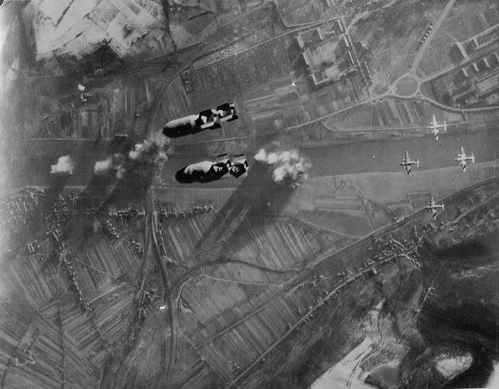 Bomb bay view of Martin B-26 Marauder bombers of the 323rd and 394th Bomb Groups drop 122 tons of bombs in an effort to take down the railroad bridge across the Moselle river at Trier Germany 24 December 1944.