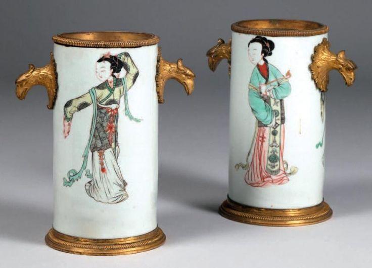 Paire de vases de forme cylindrique en porcelaine de Chine à décor polychrome de longues dames, monture en bronze doré et ciselé figurant des têtes d'aigle et une frise de godrons. XVIIIe siècle.
