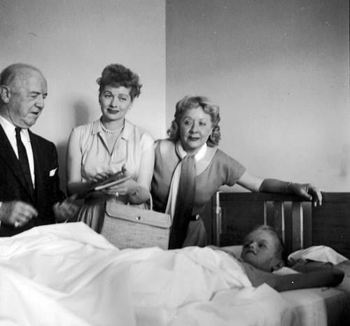Look at the sweet look on Lucy's face . . . Lucille Ball, William Frawley, and Vivian Vance visit patients at a children's hospital in New York.