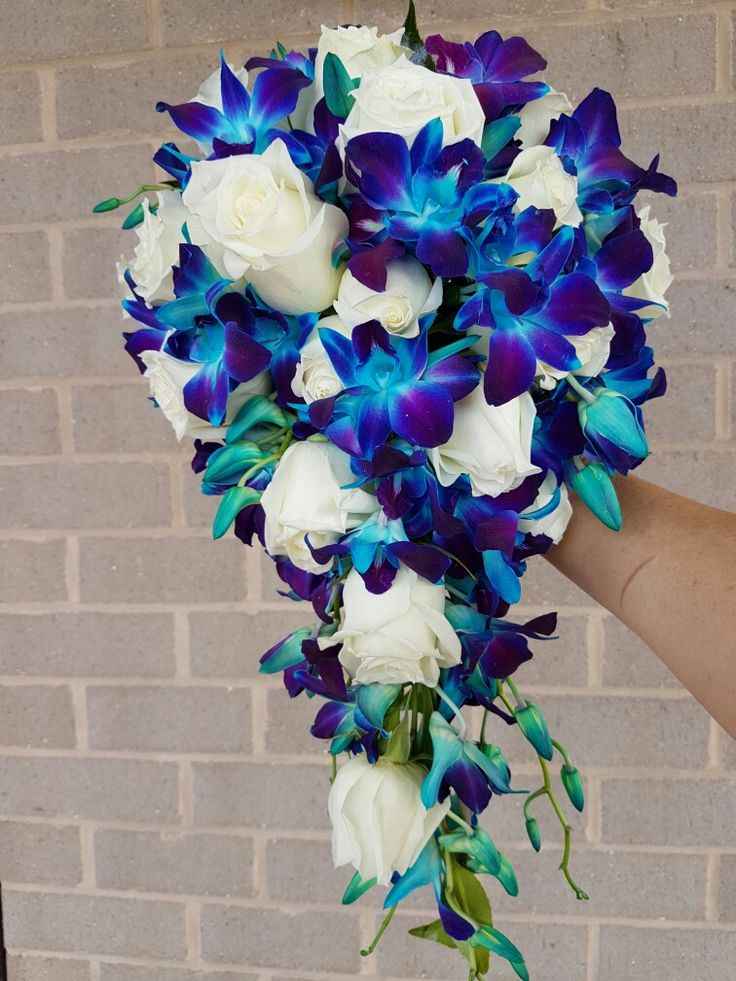 A wired tear drop bouquet of white roses with blue singapore orchids
