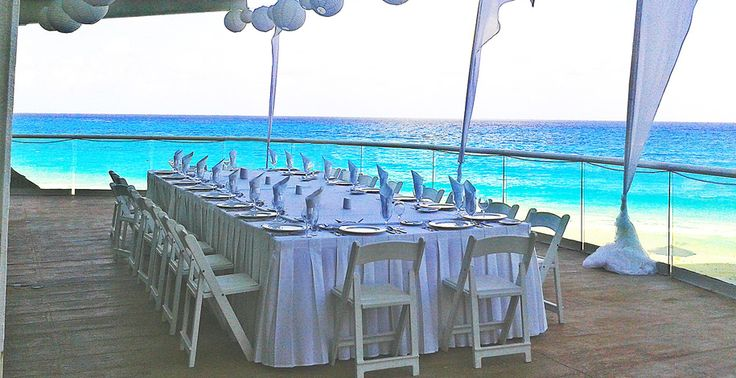 Love the white paper globe lanterns decorating this rehearsal dinner setup on the beach at Sun Palace in Cancun, Mexico | Palace Resorts #destinationwedding