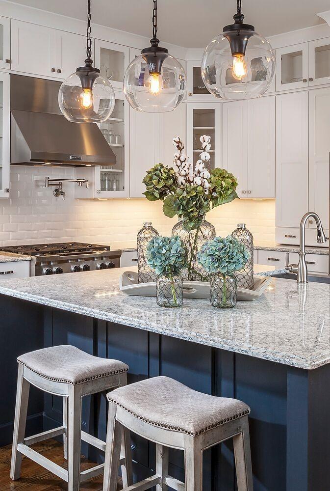 Dies ist eine weiße und dunkelblaue Küche mit Metall verzierte Vasen mit Blumen auf eine breite Marmortreppe glänzenden Arbeitsplatte akzentuiert.
