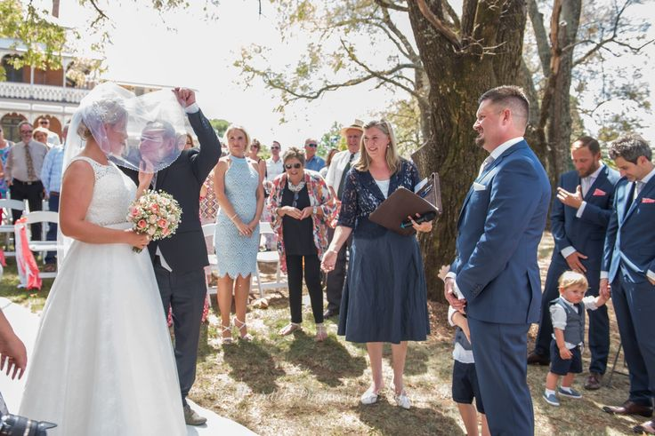 Wedding photographer, Candid Photos of a Lifetime  the Groom seeing his bride for the 1st time, while her dad gives her a kiss
