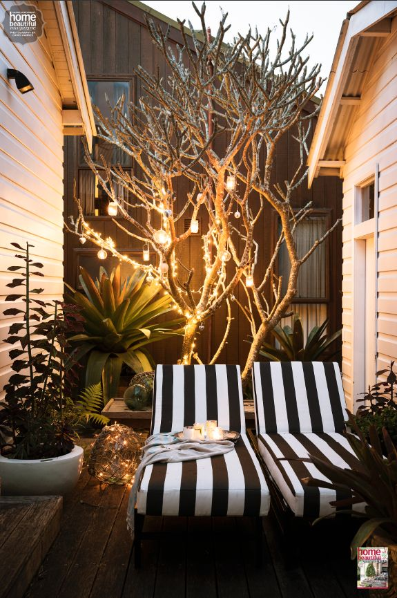 Twinkling lights and striped chairs are great for a warm-weather Christmas outside