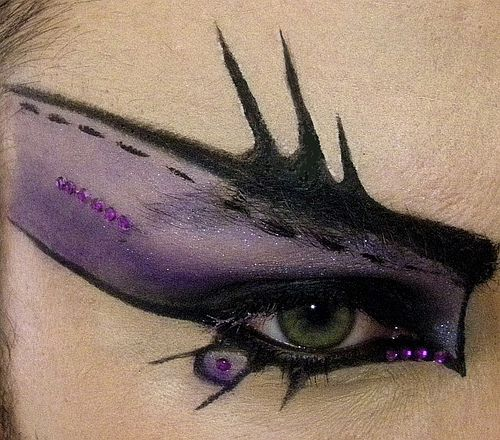 Purple and black eye makeup. Stiching and spikes upwards with sparkles
