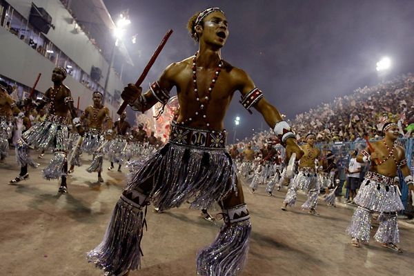 """The origins of Brazilian carnival are in the ritual dances of Black Africa, pulsating rhythms of which were brought to Brazil, along with millions of black slaves .In the mid 20th century the first school of samba was formed. In 1916, the first samba was written specifically for the carnival. It was called """"By telephone""""."""