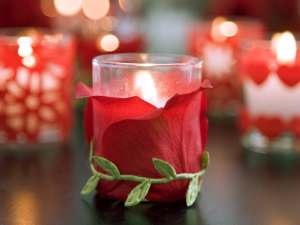 Real rose petals create an elegant candle votive. Use just a light drop of glue at the base of the petal and a vine embellishment, or even ribbon to hold it's upright position on the glass.