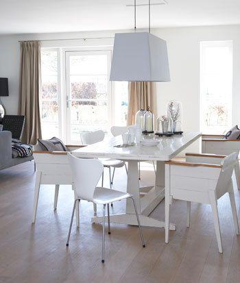 Bij de witte tafel van Piet Hein Eek staat een vlinderstoel van Arne Jacobsen.