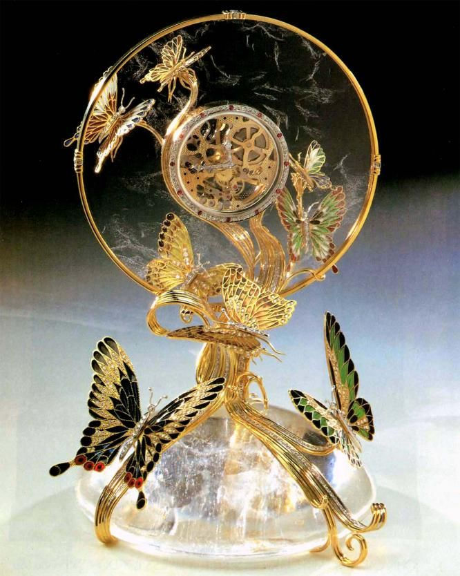 RC.Butterfly clock. An Asprey clock made by James Miller . The clock is a Baume & Mercier, eight day movement. Paul Mason (an ex Cartier watch and clockmaster), is the clock maker. The clock stands 14 inches high, made of two pieces of carved rock crystal, 18 ct, gold fittings, 18ct. gold plique-a-jour enameled butterflies and the whole piece is set with diamonds, with rubies set on the hour of the clock's rim