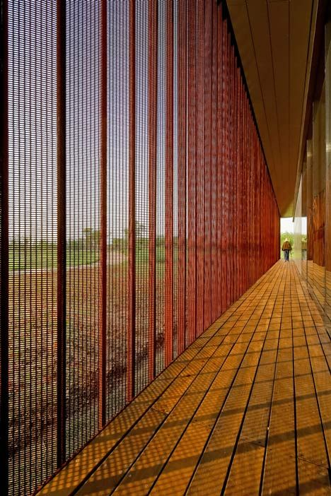 Farm visitor centre featuring a louvred wall of weathered steel mesh.