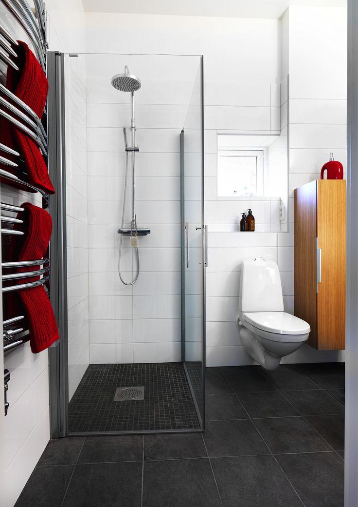 Klinkers i grått på golv, mosaik i dusch där man för fallet måste ha mindre plattor. Rostfritt avloppsgaller. Vit kakel på väggar - snyggt!