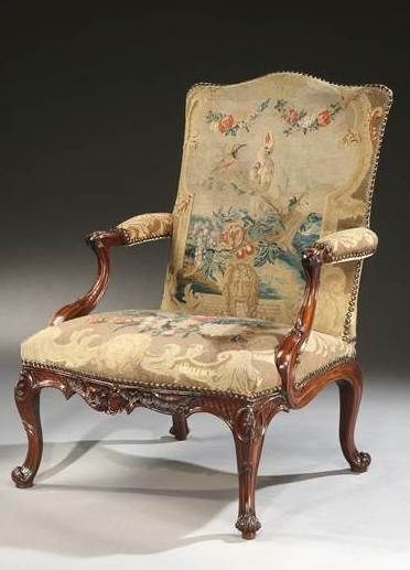 A rare pair carved mahogany Gainsborough armchairs in the manner of Th. Chippendale retaining the original gros point needlework covers,, England, ca 1755. Height: 40 ¼ in; 103 cm Width: 28 ½ in; 72.5 cm Depth: 27 ¾ in; 70.5 cm