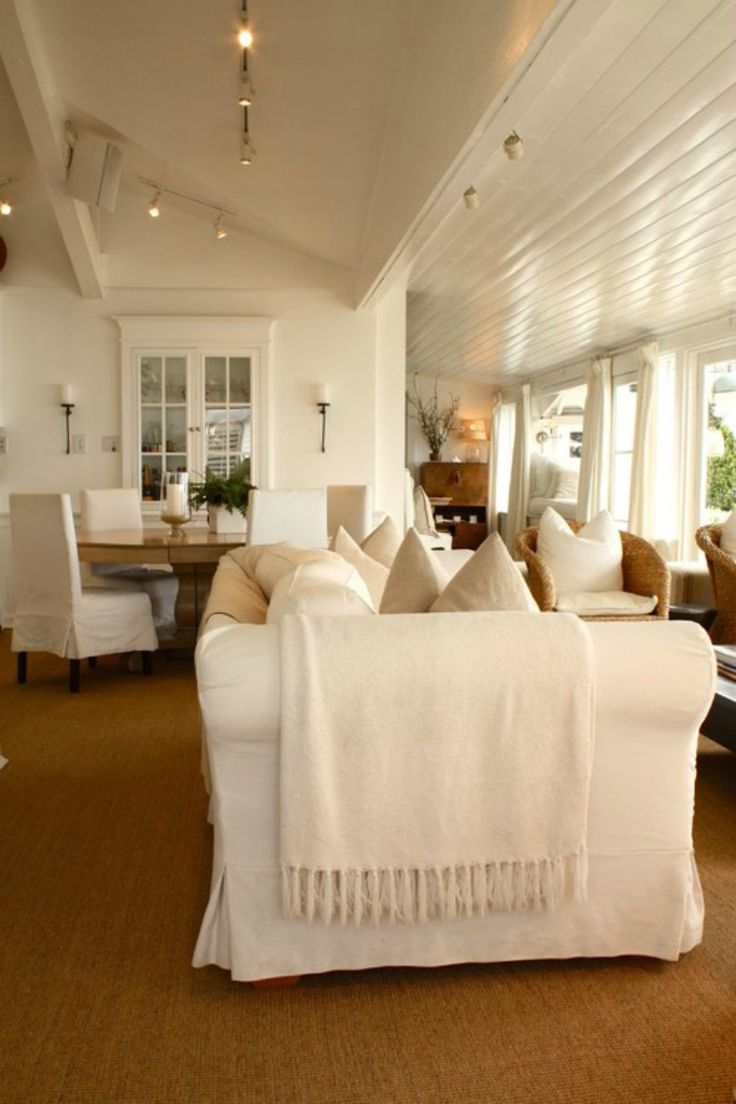 Beach house great room with coastal white slipcover couch, white wood plank ceiling, white cabinet against white wall