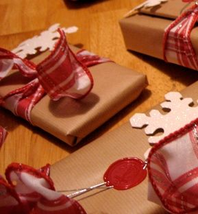Kraft paper packages with snowflakes held by a wax seal.