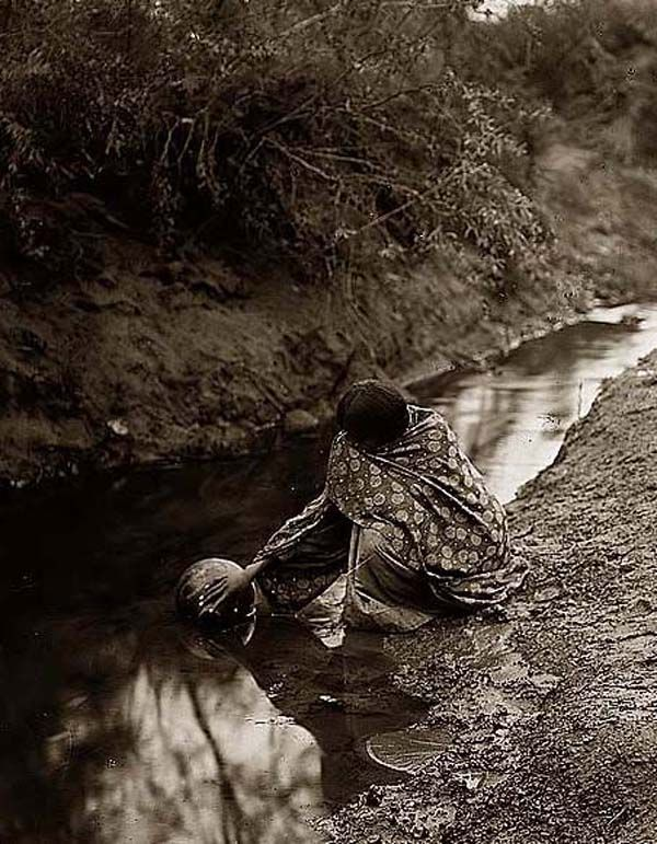 Here for your browsing pleasure is a majestic photo of a Maricopa Water Girl. It was made in 1907 by Edward S. Curtis.    The illustration documents a Maricopa woman squatting beside a stream filling jher ug with water.    We have compiled this collection of artwork mainly to serve as a vital educational resource. Contact curator@old-picture.com.    Image ID# CC51C98A