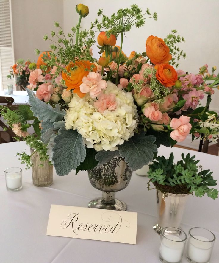 reception  table arrangement of white hydrangea, peach stock, orange ranunculus,  queen anne's lace, dusty miller, peach mini carnations, jasmine vine and seeded eucalyptus in a footed mercury glass compote is surrounded by votives and a succulent in a silver julep cup.