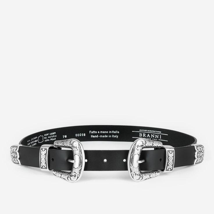 Cinturón de cuero negro con hebilla y puntal doble, ambos de latón plateado con florituras. Es el cinturón del momento, versátil y espectacular.