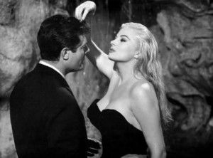 """With La Dolce Vita (1960), director Federico Fellini submitted a singular classic. True, considered strictly as a film—as a three-hour film starring Marcello Mastroianni as a gossip reporter with perfect hair—it is tediously baggy, a movie """"about the boredom of boring people"""" provisionally employed in """"the various whoring professions,"""" to quote David Thomson. But judged … Continue reading The Greatest Non-Kiss in the History of Cinema →"""