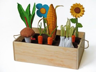 Orto in pannolenci e feltro con scatola in legno munita di manici per trasportarla facilmente.E' composto da: 1 pannocchia, 3 carote, 1 fungo, 1 finocchio, 1 barbabietola, 1 fiore, 1 girasole. All'interno ci sono 3 salsicciotti estraibili in juta ( imbottiti con ovatta anallergico) divisi tra di loro, tra i quali si possono piantare o raccogliere gli ortaggi e i fiori