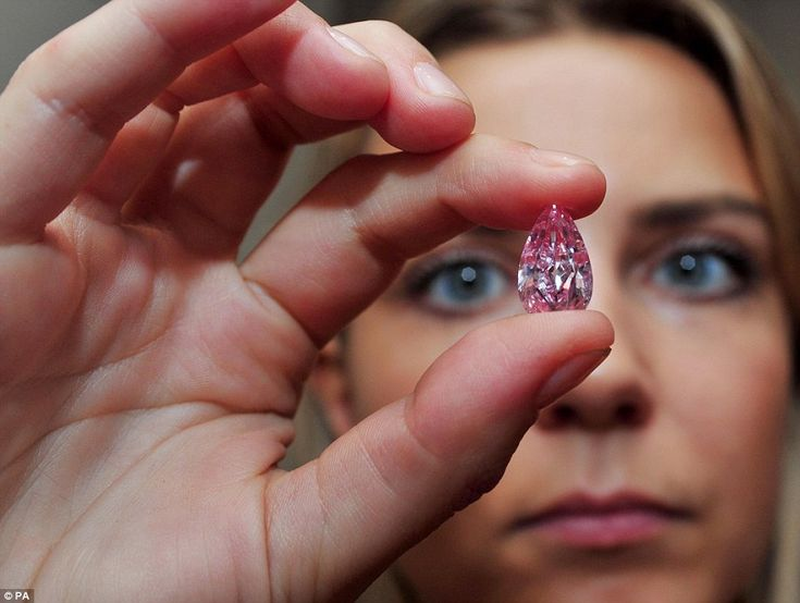 A sales assistant shows off the rare 8.41 Carat pear-shaped internally flawless fancy vivid purple-pink diamond, which sold in October 2014 for $17.7million