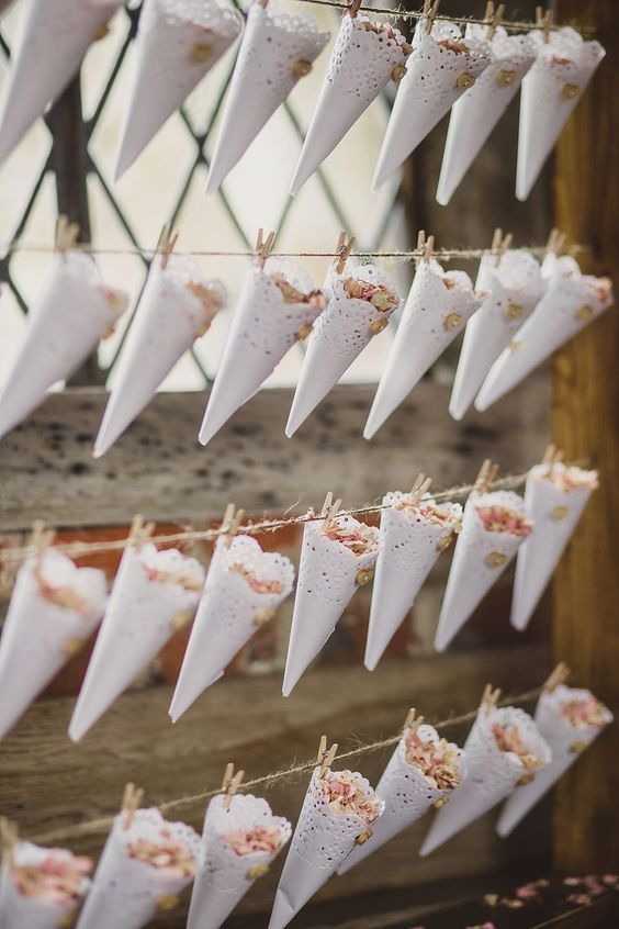 Lace doily confetti cones pegged to a wooden frame
