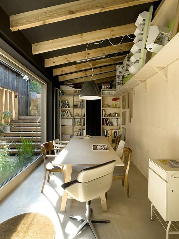 Il pavimento in linoleum chiaro contrasta gradevolmente con il soffitto dipinto di scuro, mentre le travi sono lasciate a vista. A1 Architects