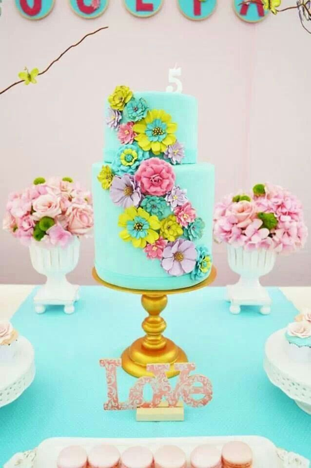 Blue cake adorned with colorful blooms