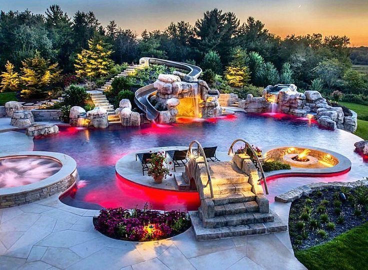 FULLY LOADED heated swimming pool with a hot-tub, lazy river, waterslide, island, bridge, infinity edge, cave, sunk in fire pit, waterfalls, AND customizable LED lighting … Tag someone that would die over this! #ModernMansions