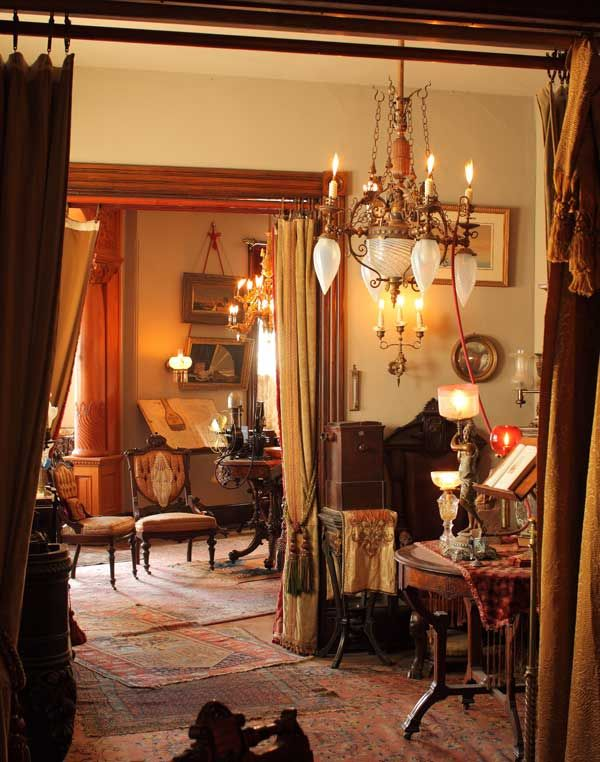 A view from the back parlor hints at the collection of Victorian lighting and antiques. A lamp on the center table below is connected, in the Victorian fashion, to the gasolier above by a rubber hose.