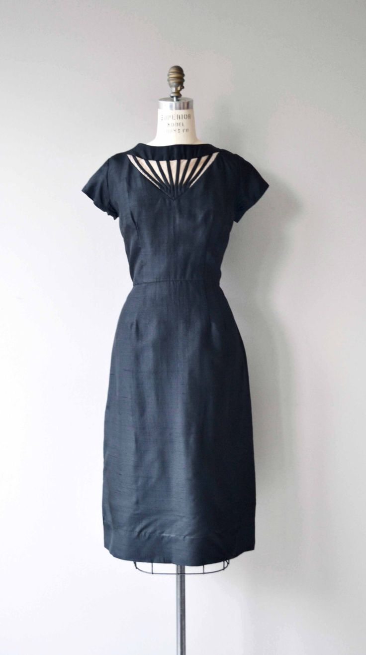 Vintage 1950s black silk cocktail dress with trapunto illusion neckline, short sleeves, fitted waist and metal zipper. --- M E A S U R E M E N T S --- fits like: medium bust: 38-40 waist: 30 hip: up to 42 length: 44 brand/maker: n/a condition: excellent to ensure a good fit, please read the sizing guide: http://www.etsy.com/shop/DearGolden/policy ✩ more vintage dresses ✩ http://www.etsy.com/shop/DearGolden?section_id=5986725 ✩ vi...